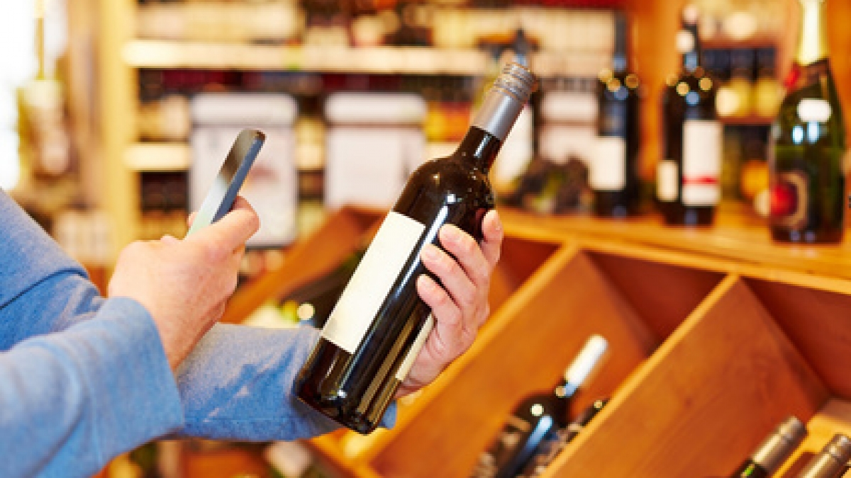 Hand with smartphone scanning wine bottle in supermarket for price comparison